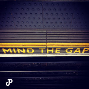A photo of a London train station that reads, Mind the Gap