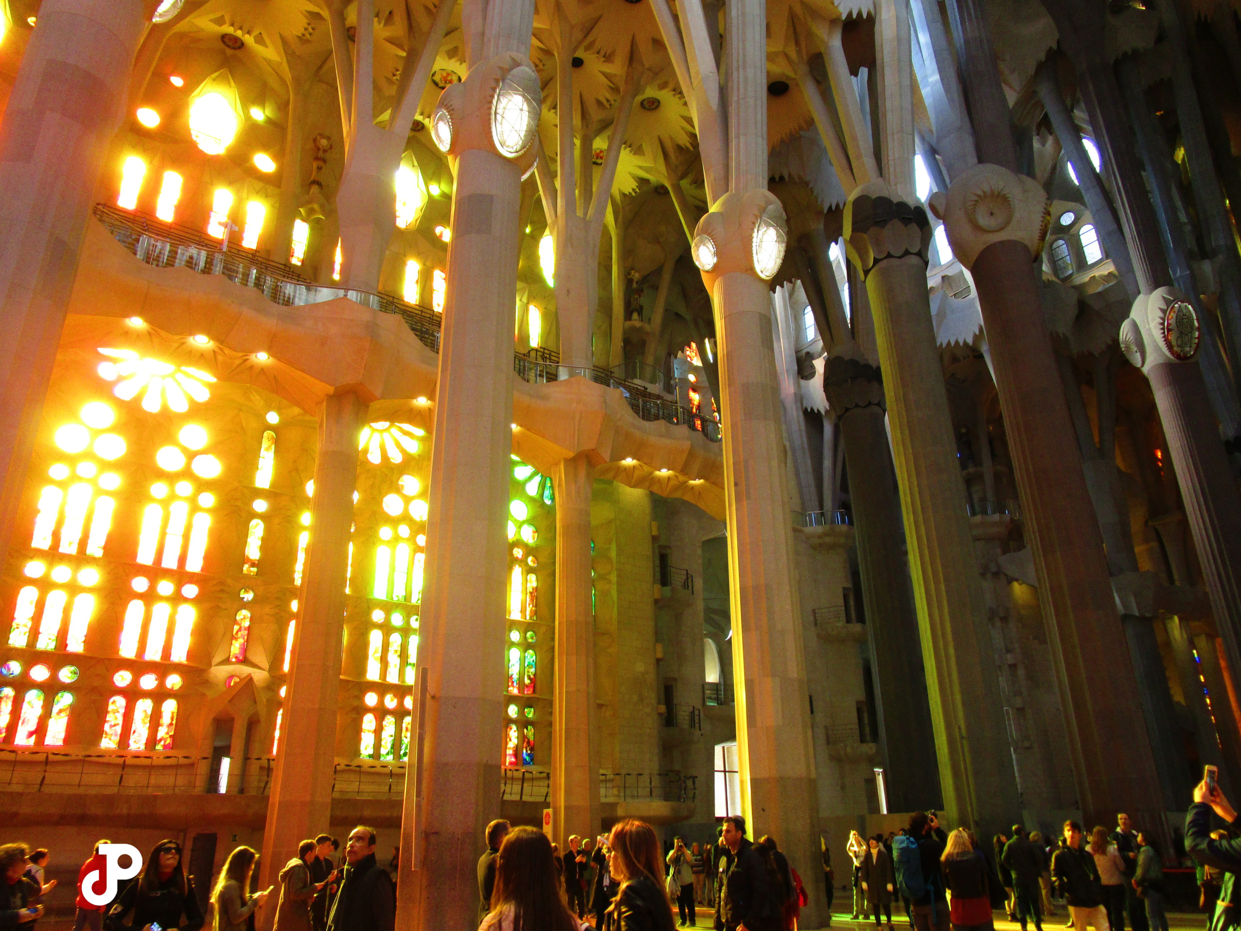 sunlight filtering through the colorful stained glass windows of La Sagrada Familia, washing the interior in bright orange light