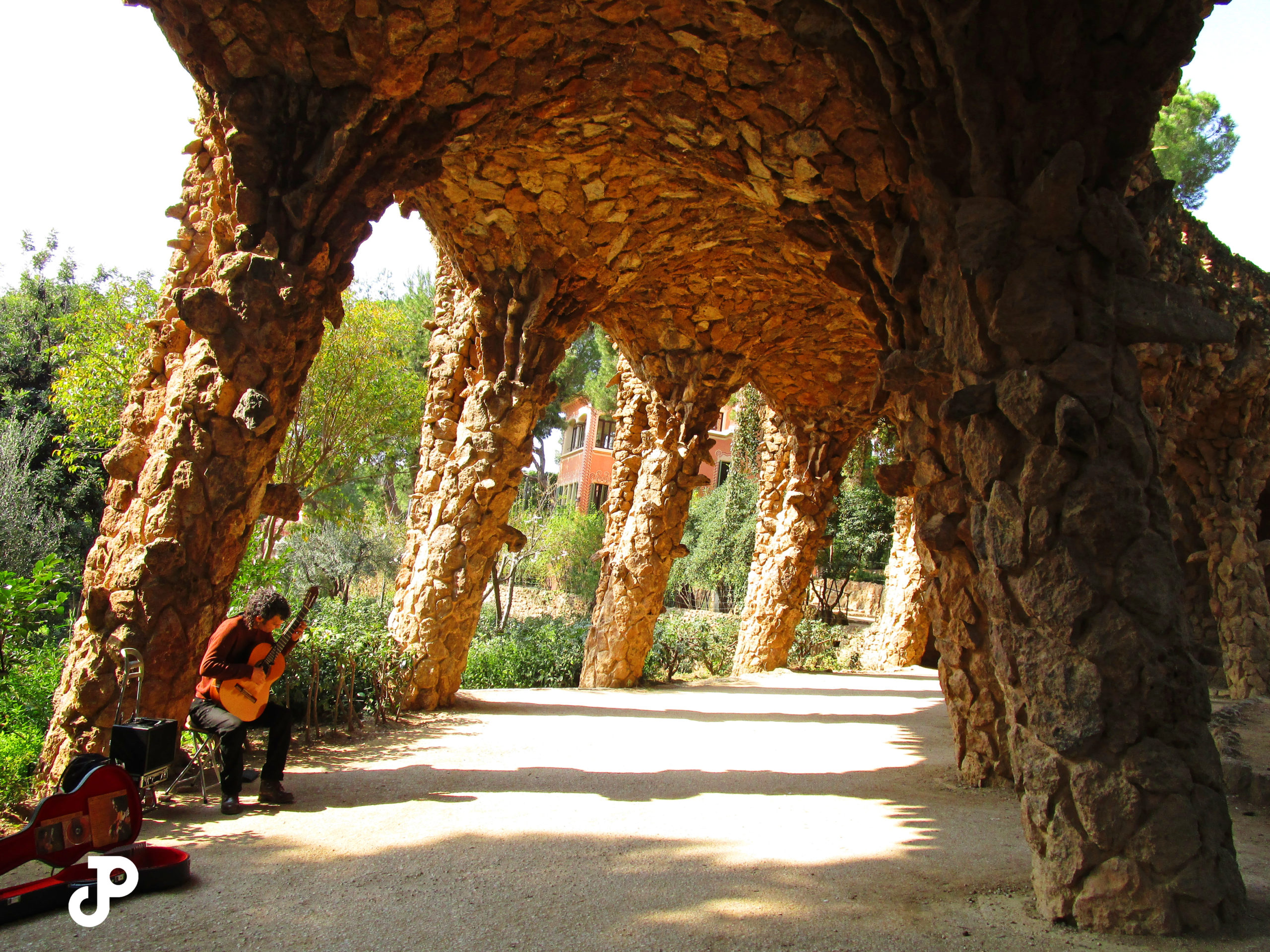 a man playing guitar beneath a stone archway in Park Guell