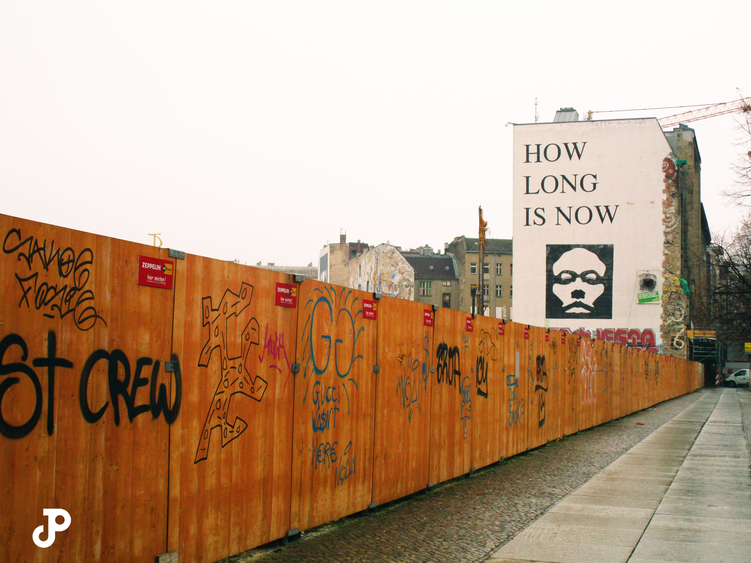 a wooden fence covered in graffiti leading to a building in the distance, which is painted with a mural that reads, how soon is now?