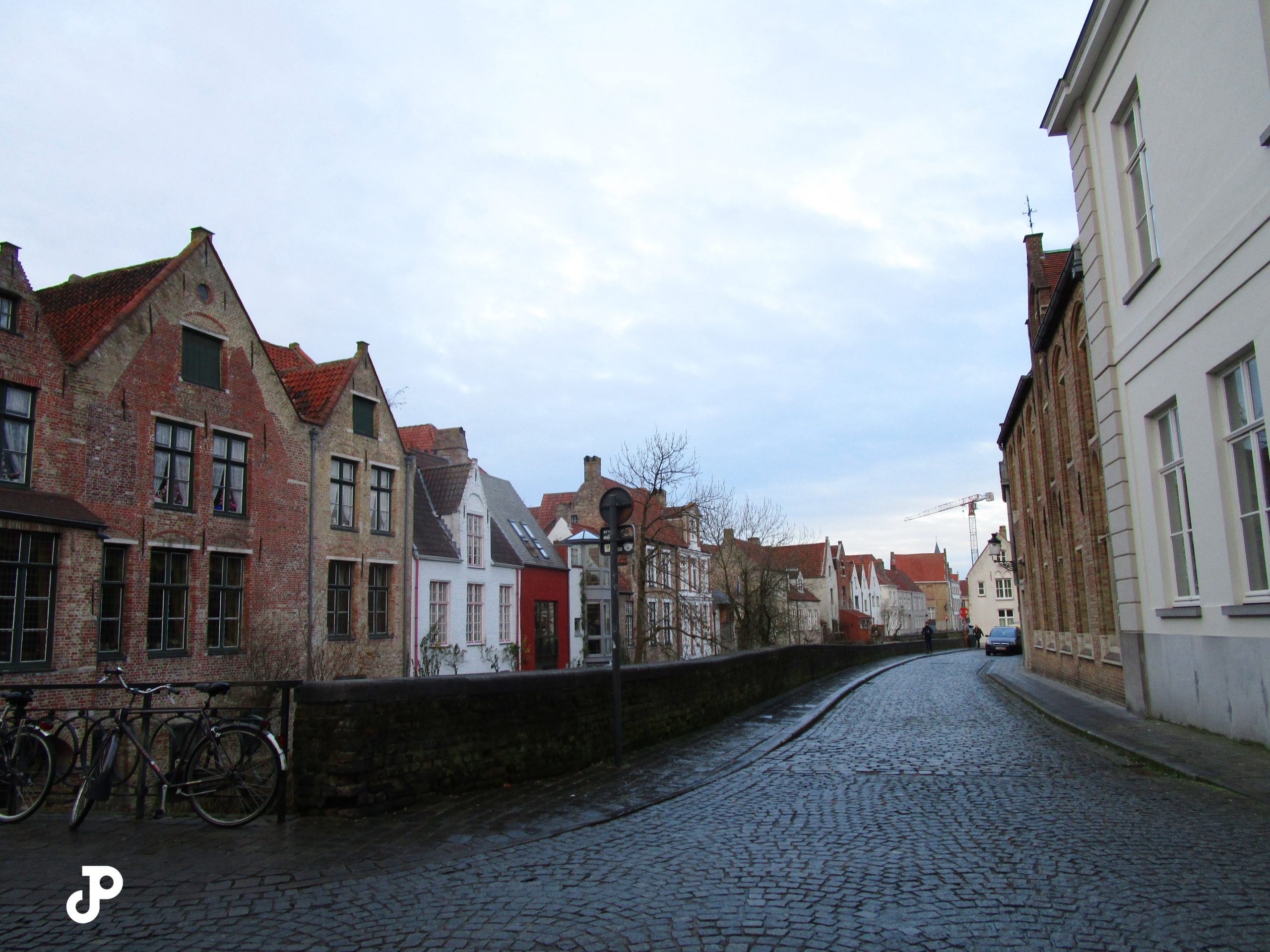 a cobblestoned street lined with old brick buildings with pointed rooves
