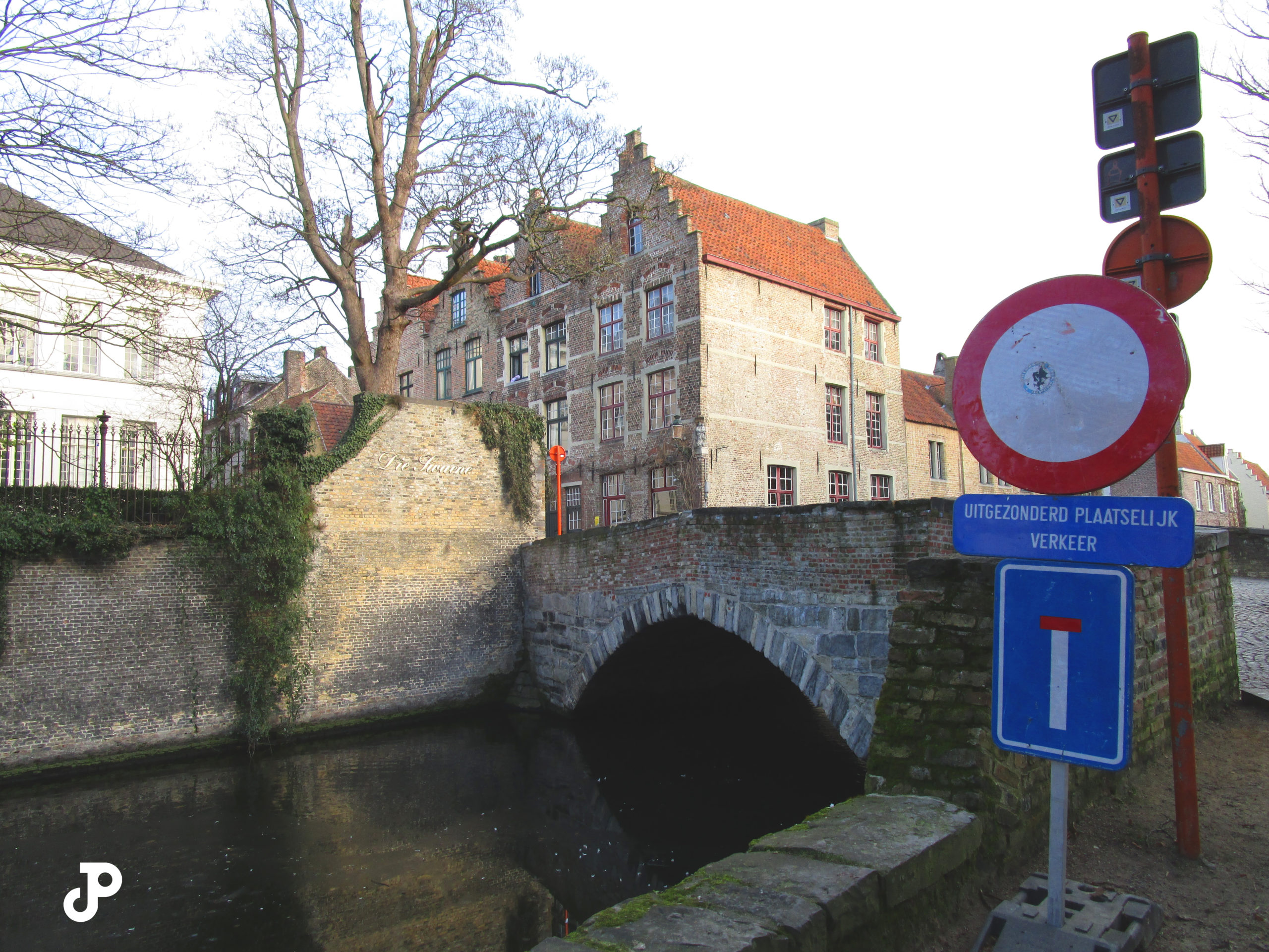 a brick bridge spanning a narrow canal