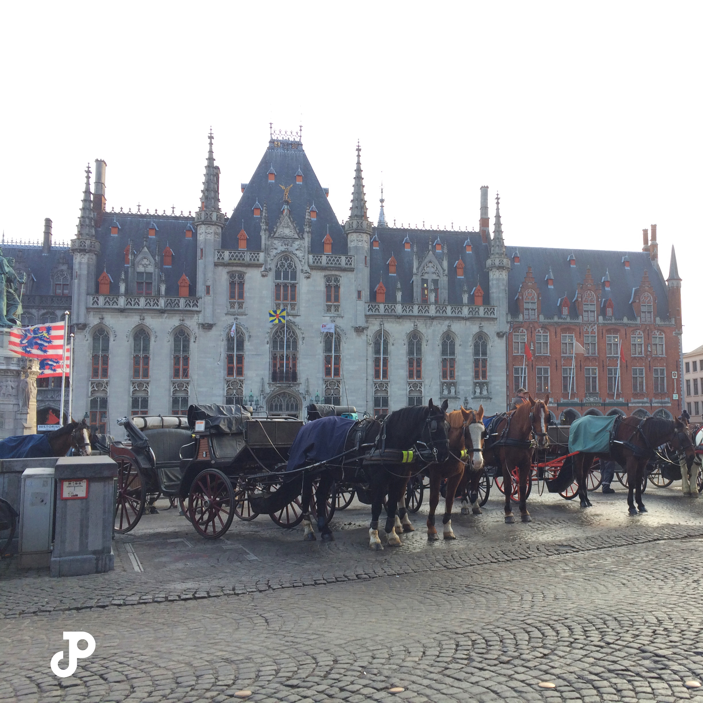 horses and carriages lined up in Burg Square, with the Bruges City Hall in the background