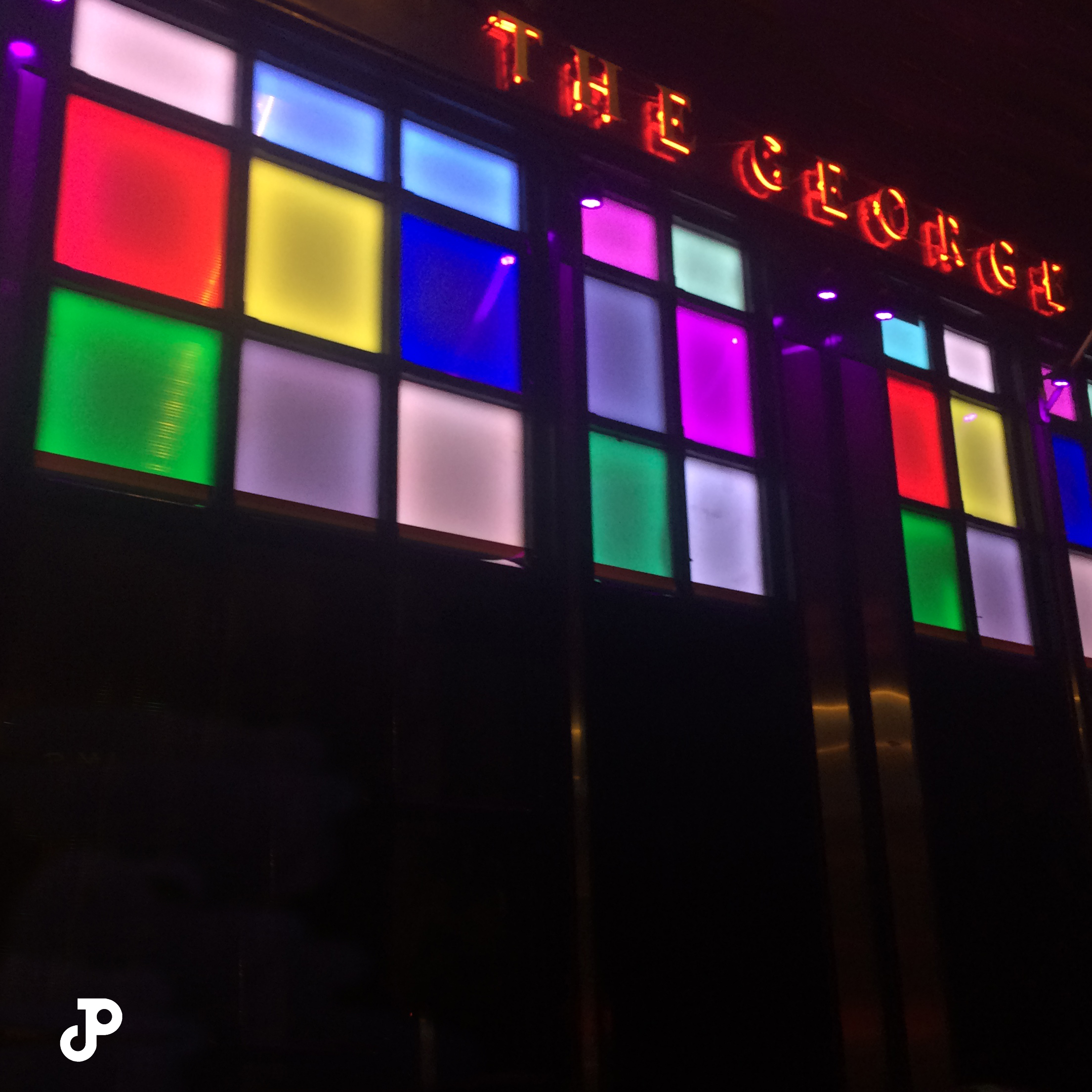 the outside of The George pub, which has colorful stained glass windows and a red neon sign