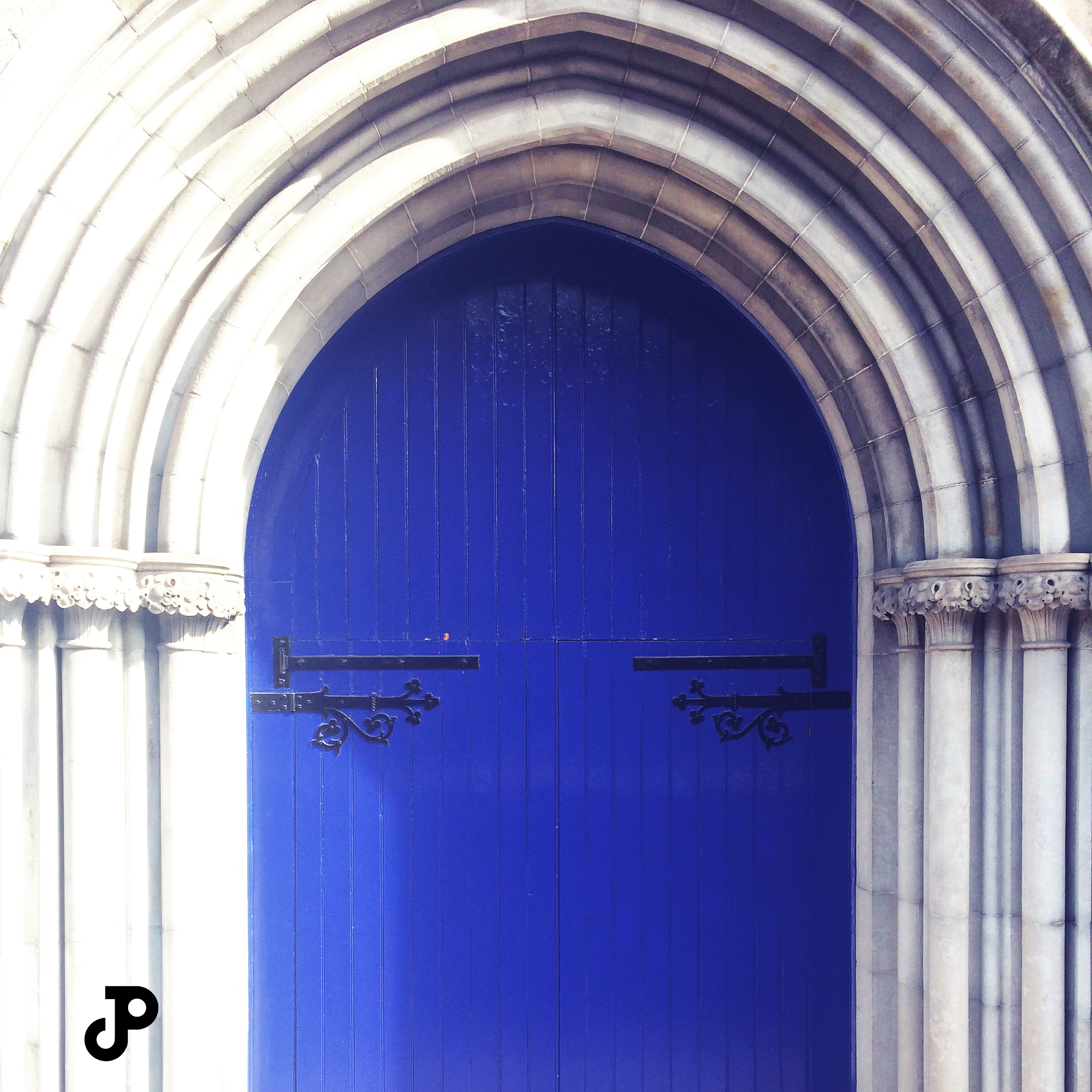 an arching, medieval door, painted a vibrant shade of blue, at Saint Patrick's Cathedral