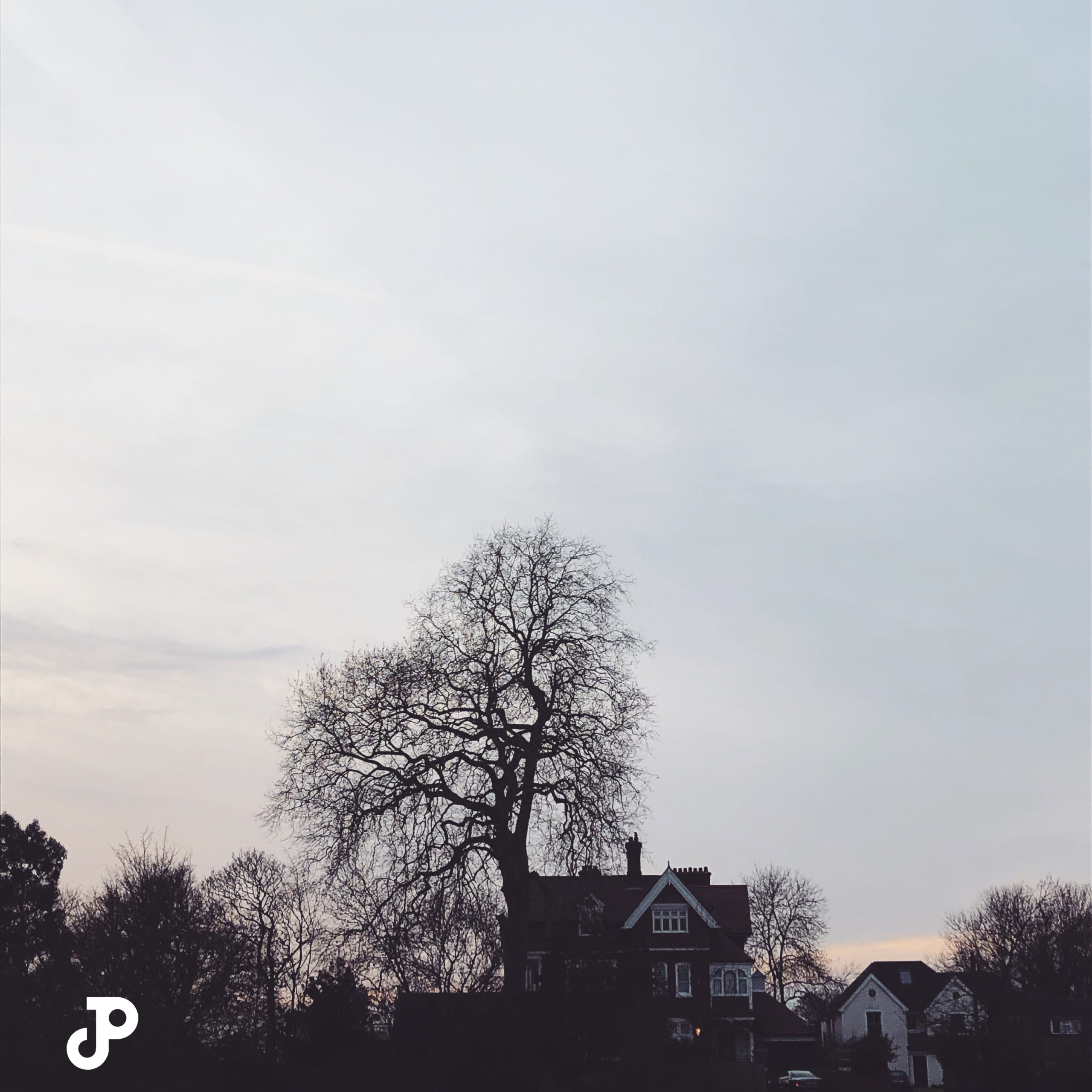 the silhouettes of a cottage and tree at twilight in Kingston Upon Thames