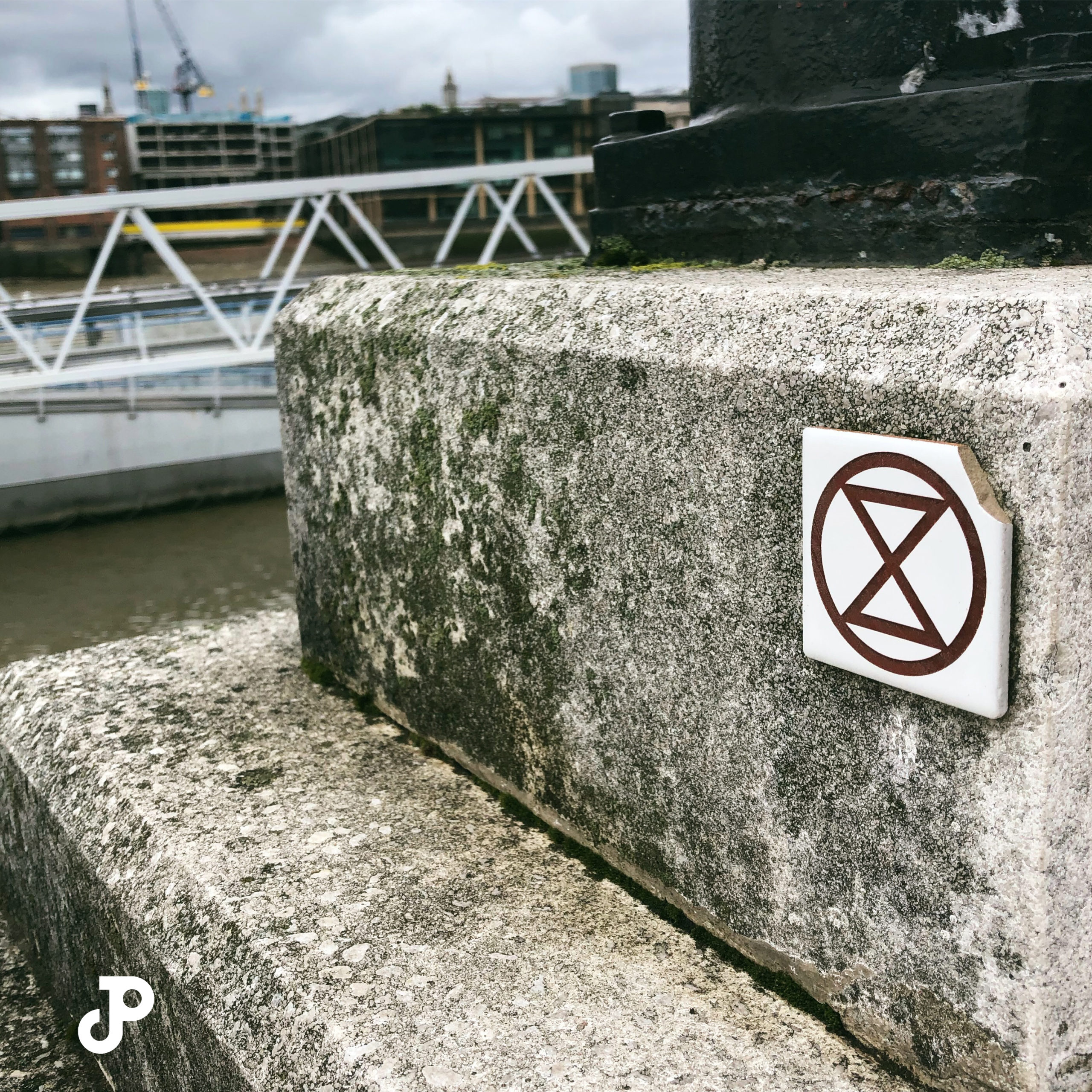 a small tile on a concrete slab, showing the Extinction Rebellion logo
