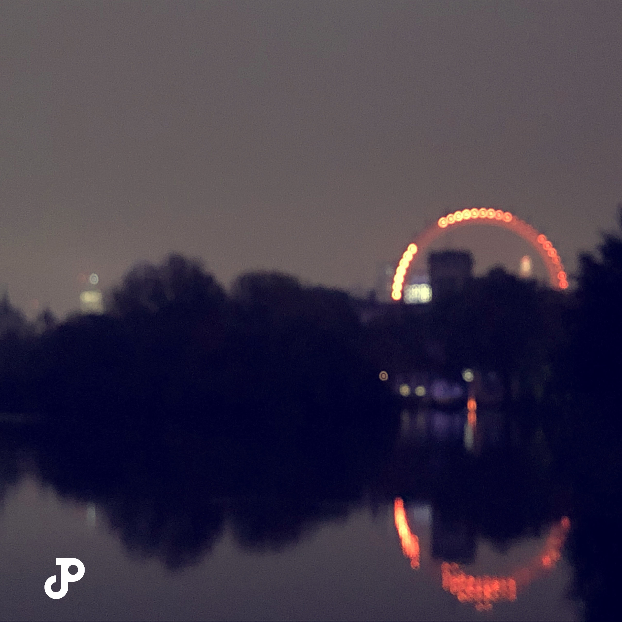 a blurred view of the London Eye seen from Saint James Park at twilight