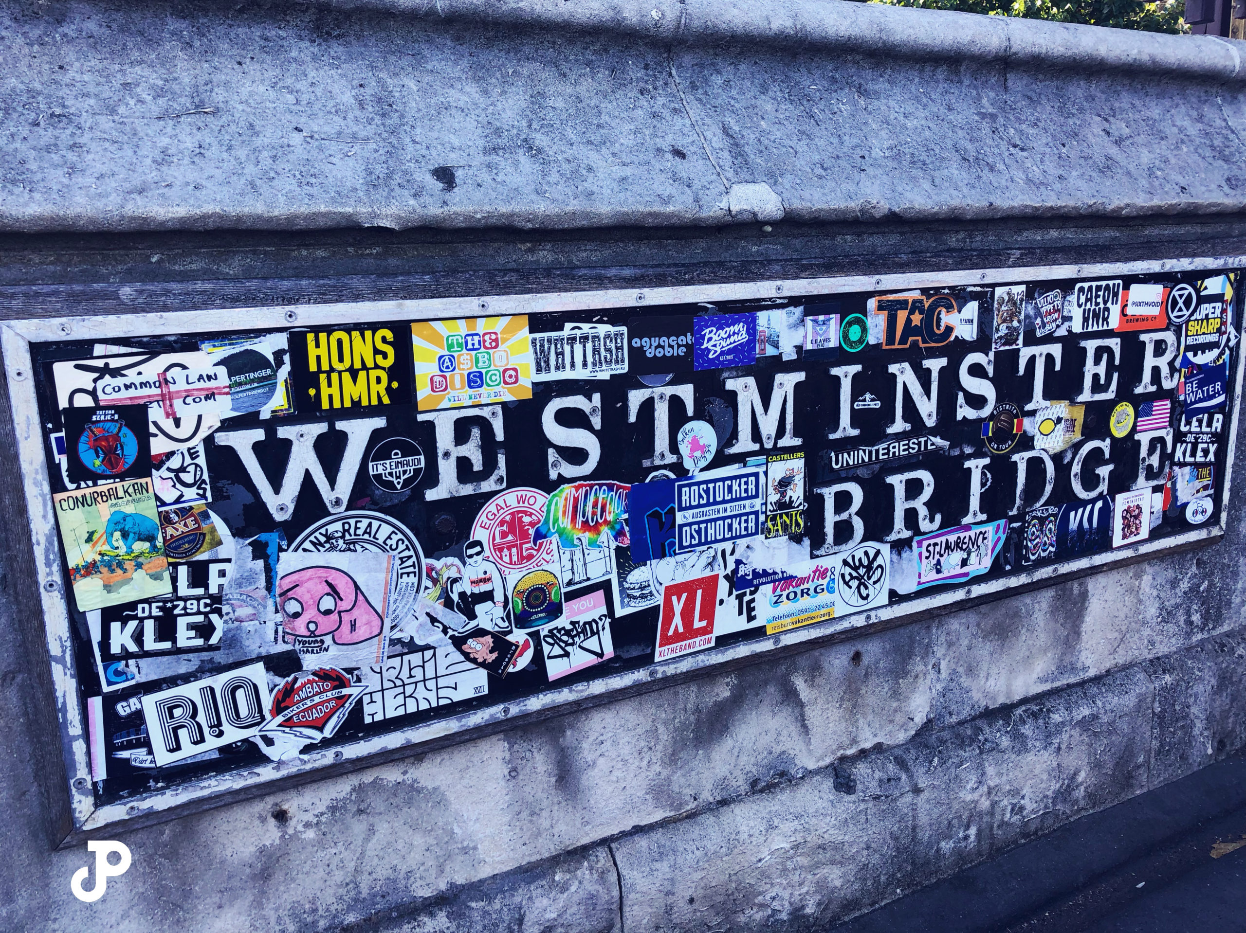 a sticker-covered sign that reads Westminster Bridge