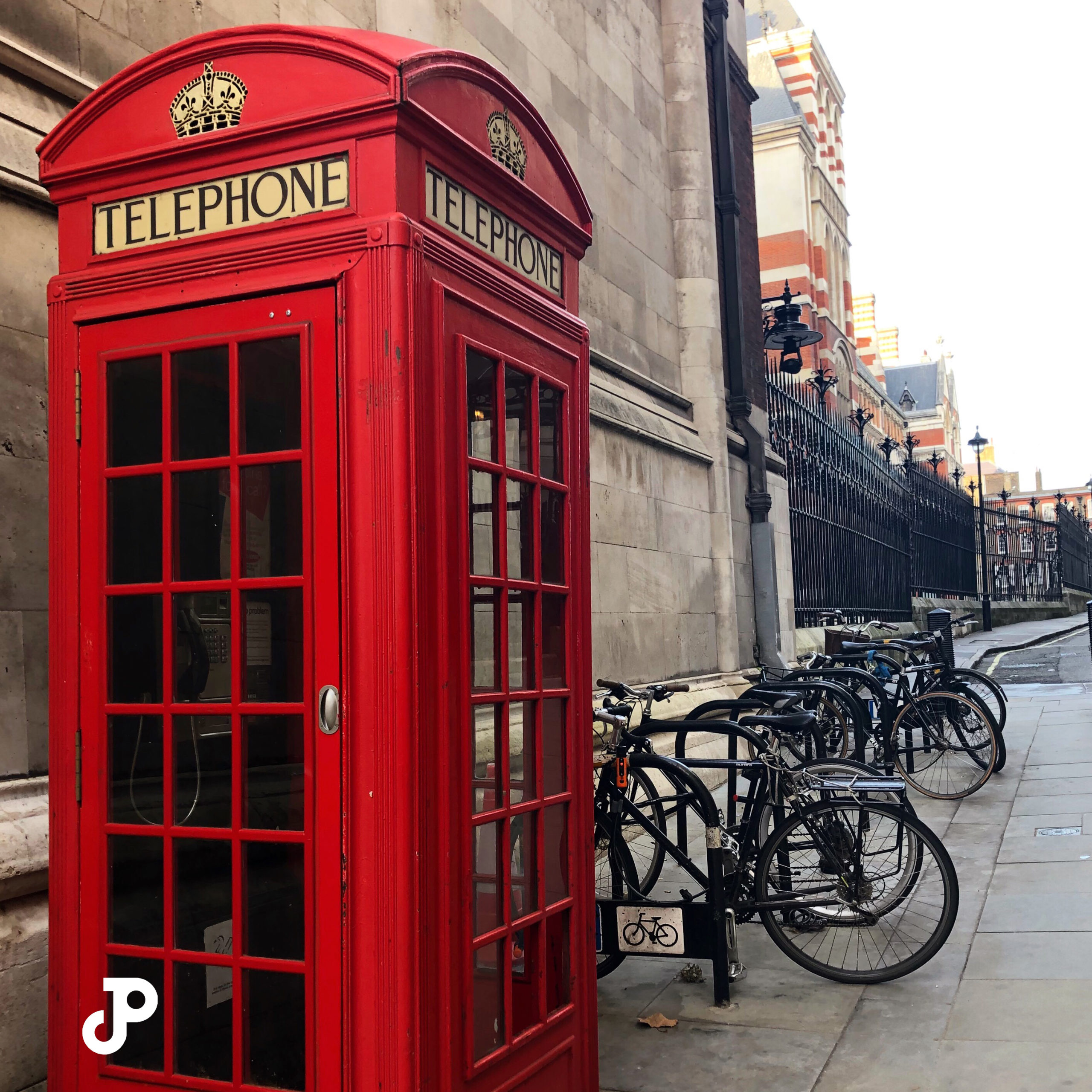 a red phone booth beside a row of bicycles in London
