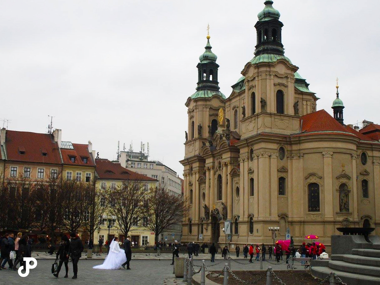 a bride and groom walking through Old Town Square