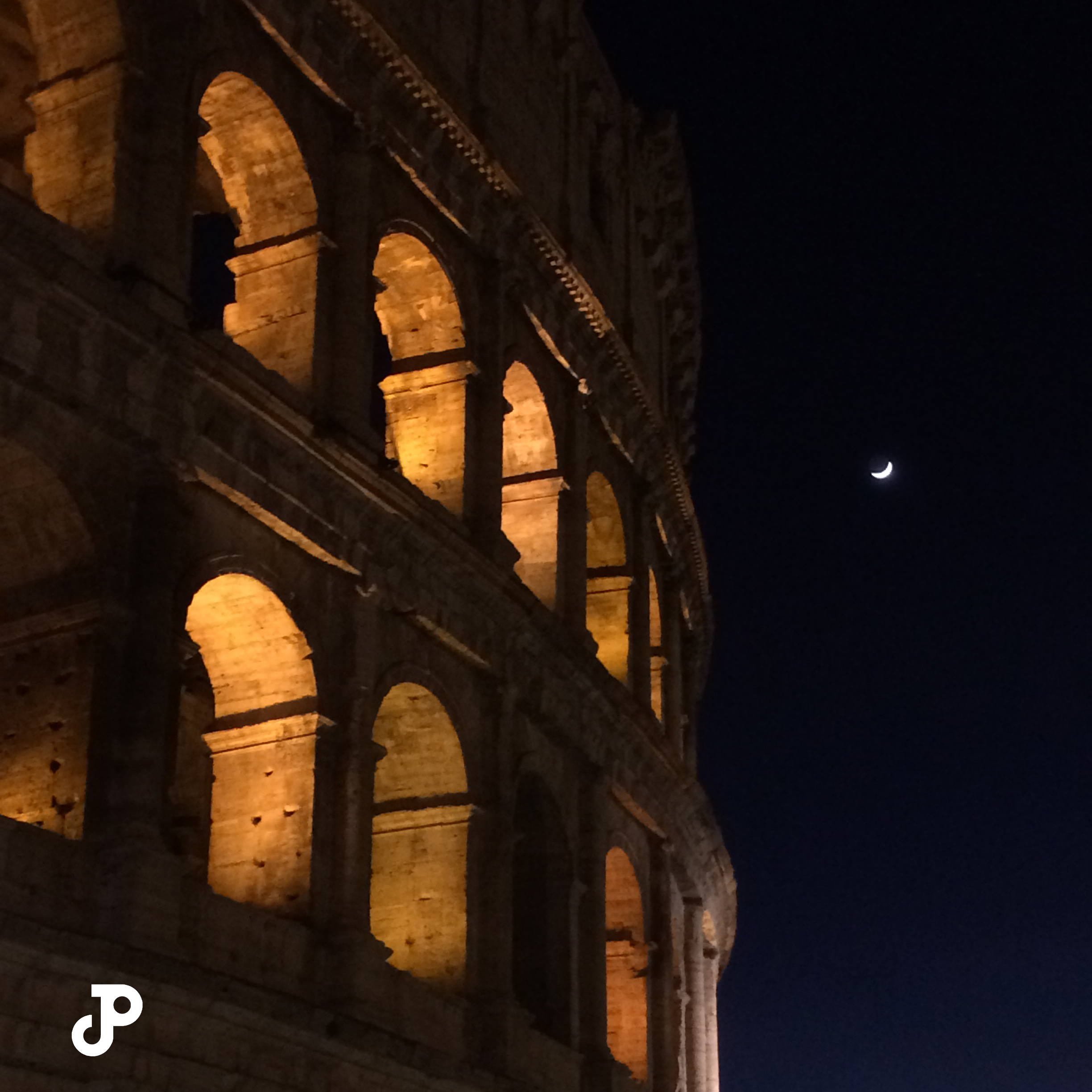 the Colosseum at night with its arches illuminated in gold light, and a crescent moon visible in the black sky