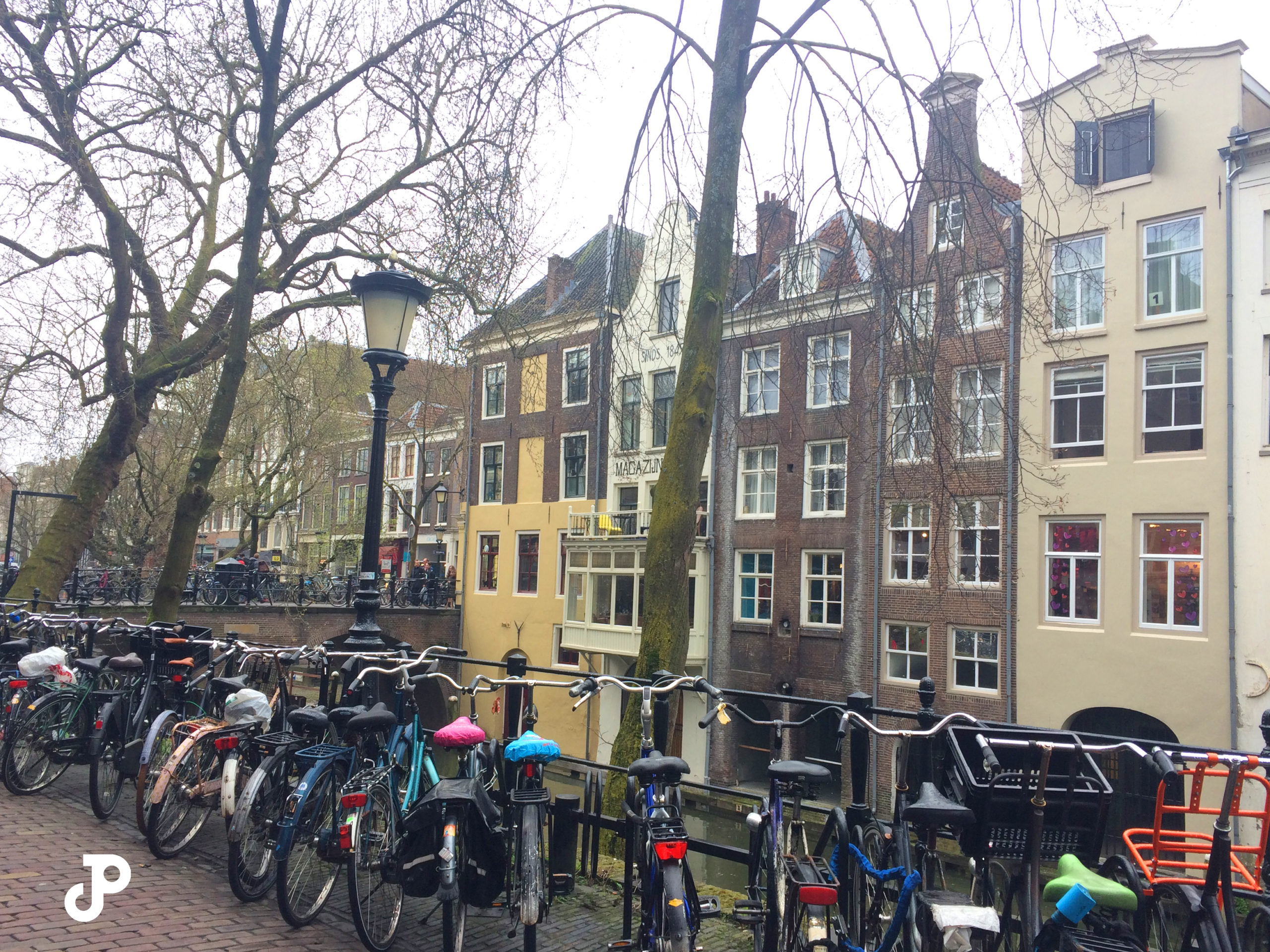 a line of bicycles along a canal with iconic narrow Dutch buildings in the background