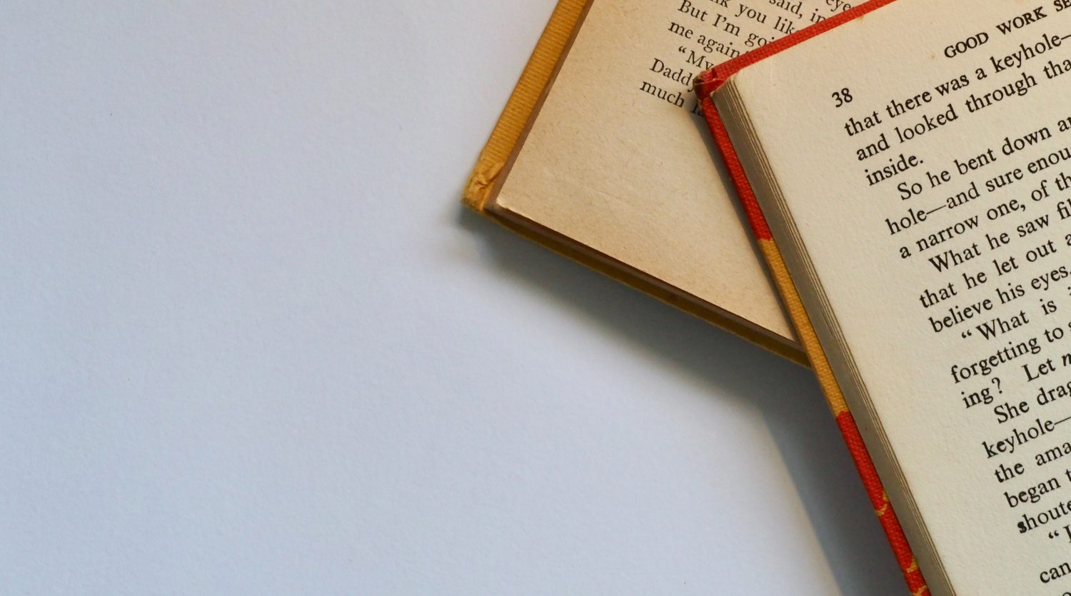 A close up image of pages from two print books, one laid above the other