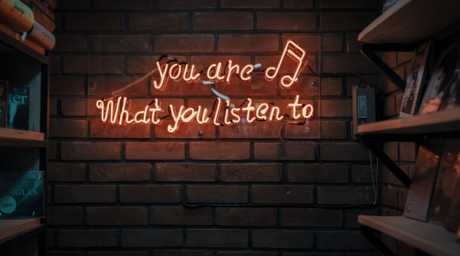 A stylised neon sign that reads you are what you listen to