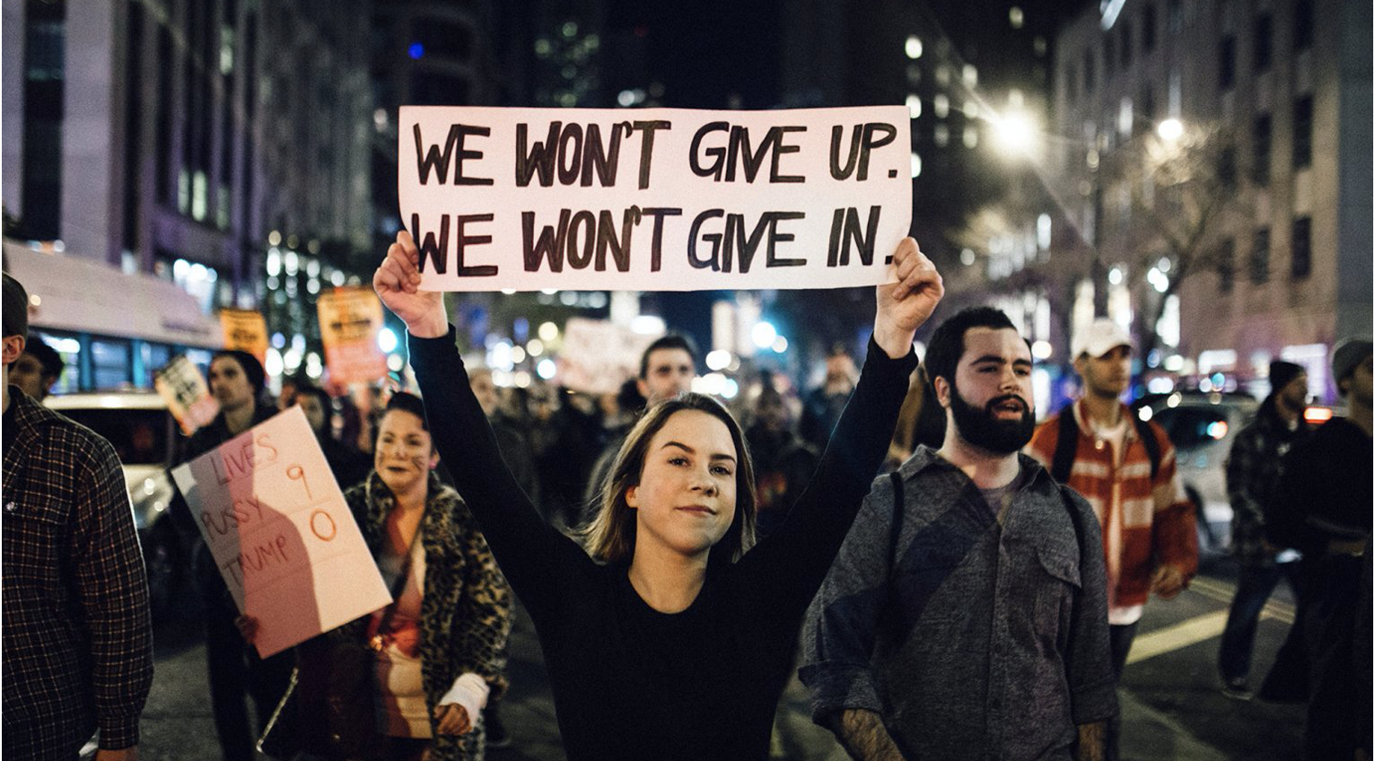 People at a protest, with a woman in the foreground holding a sign that reads, we won't give up, we won't give in