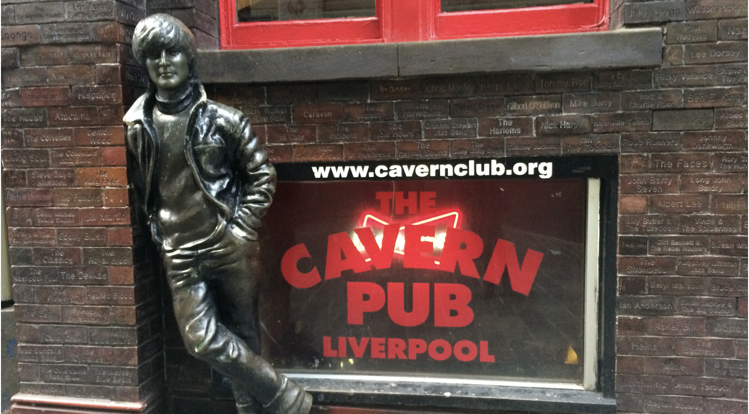 A statue of John Lennon standing beside a glass window with red painted letters that read The Cavern Plub Liverpool